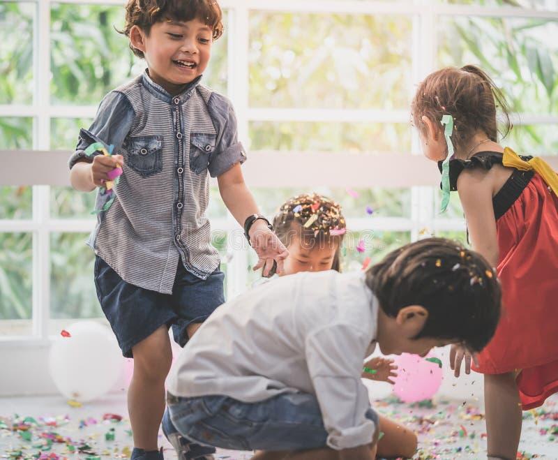Ungar som spelar och kastar papper och ballongen i ungeparti royaltyfria foton