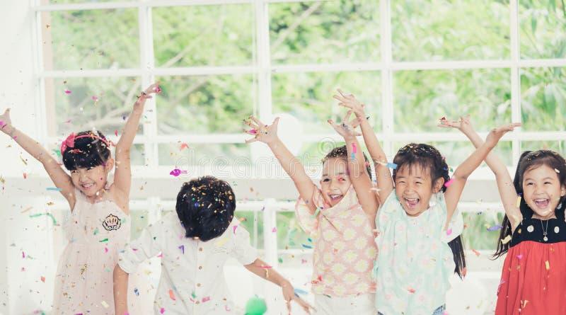 Ungar som spelar och kastar papper i ungeparti royaltyfri foto