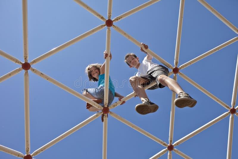 Ungar som spelar på apastänger royaltyfri foto