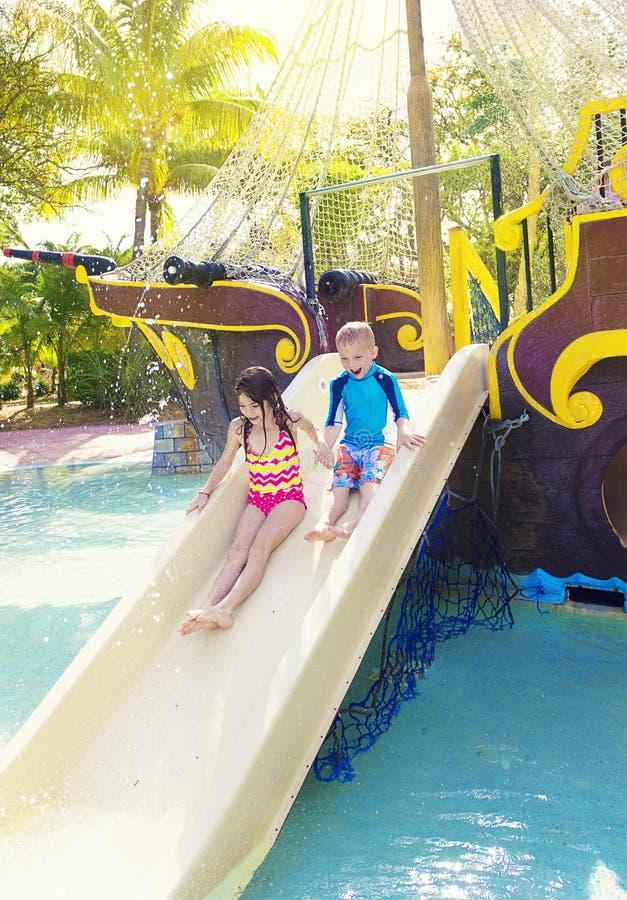 Ungar som spelar på en vattenglidbana på en waterpark arkivfoton