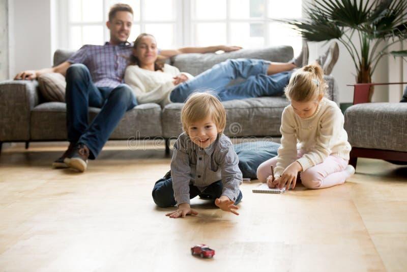 Ungar som spelar på golv, föräldrar som hemma kopplar av på soffan arkivbilder