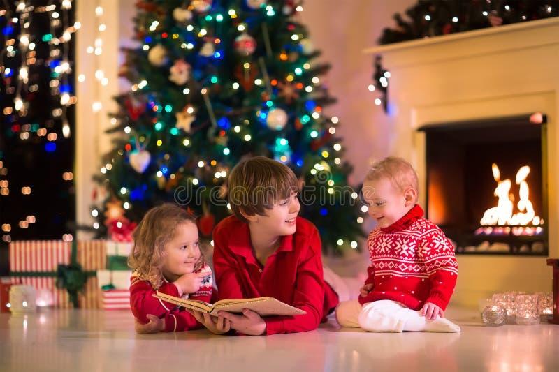 Ungar som spelar på spisen på julhelgdagsafton arkivbilder