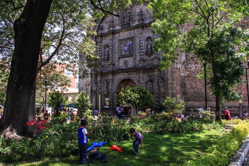 Ungar som spelar runt om en gatamarknad vid en kyrka, Guadalajara, Jalisco, Mexico royaltyfri fotografi