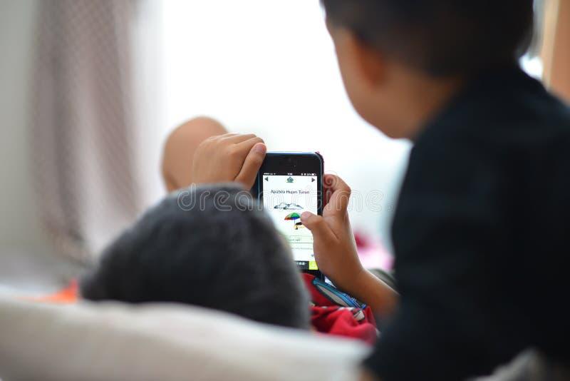 Ungar som spelar smartphonen royaltyfri fotografi