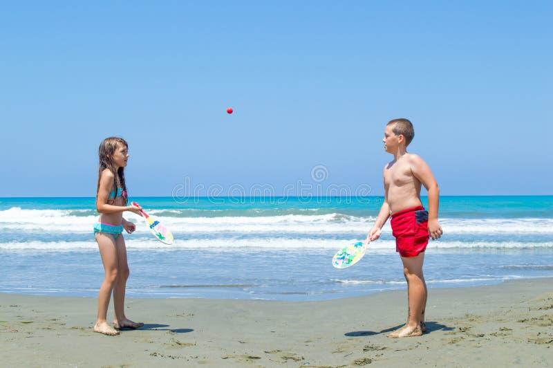 Ungar som spelar strandbollen arkivbilder