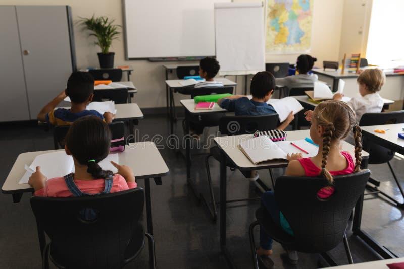 Ungar som studerar i klassrumet som sitter på skrivbord i skola arkivfoton