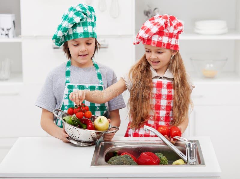 Ungar som tvättar grönsaker i köket royaltyfria bilder