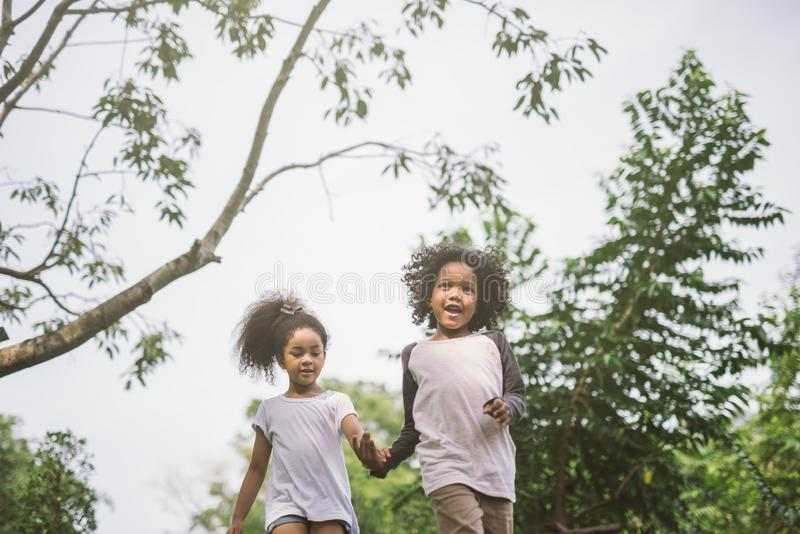 Ungar som utomhus spelar med vänner arkivfoto