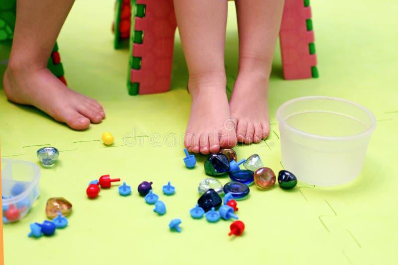 Ungar spelar med mosaikstycken, exponeringsglasstenar Ortopedisk lek, gymnastik med valgus, massage och stimulans av musklerna av arkivbilder