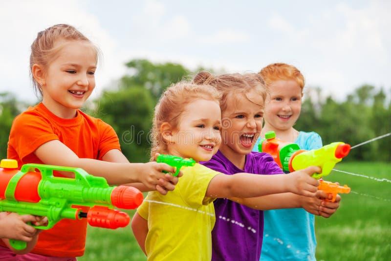 Ungar spelar med vattenvapen på en äng royaltyfri bild