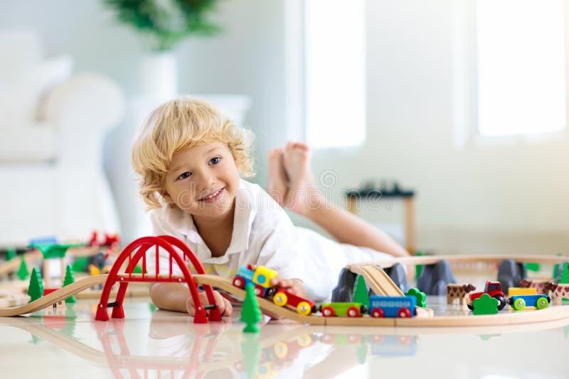 Ungar spelar träjärnvägen Barn med leksakdrevet royaltyfria bilder