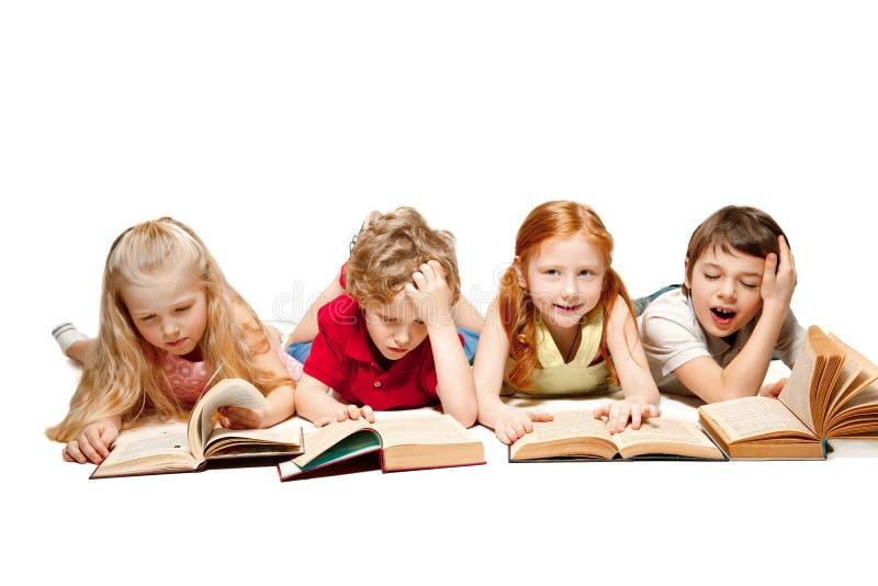 Ungarna pojke och flickor som lägger med böcker som isoleras på vit royaltyfria bilder