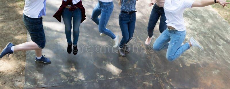 Ungdom i jeans och Keds spring och banhoppning arkivfoton