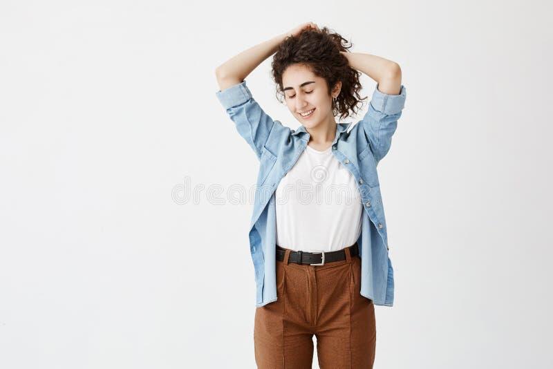 Ungdom- och lyckabegrepp Tonårs- flicka för brunett i grov bomullstvillskjorta- och bruntbyxa som poserar mot vit bakgrund royaltyfri bild