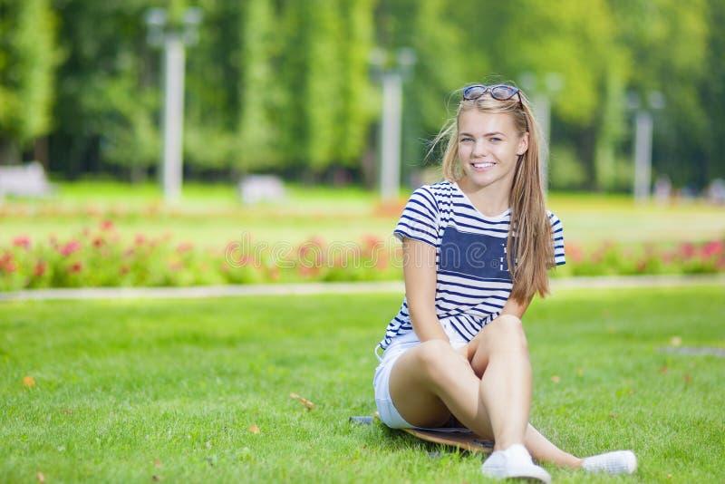 Ungdom- och tonåringlivsstilbegrepp Gulligt och le den Caucasian blonda tonårs- flickan med Longboard i grön sommar parkera arkivfoto