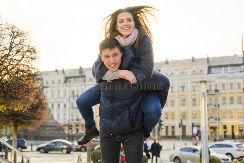 Ungdom som har gyckel i v?rstaden, den h?rliga roliga unga mannen och kvinnan, guld- timme royaltyfria foton