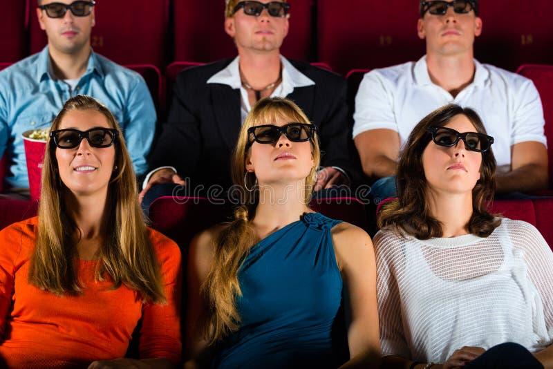 Ungdomar ansträngd hållande ögonen på film 3d på filmbiografen royaltyfria foton