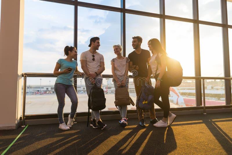 Ungdomargrupp i flygplatsvardagsrum nära Windows den väntande avvikelsen som talar lyckliga vänner för leendeblandninglopp royaltyfri bild