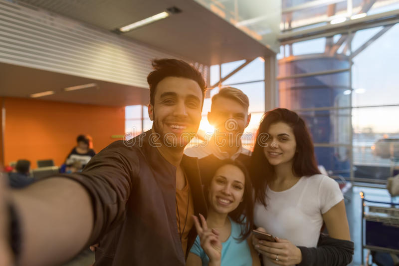 Ungdomargrupp i vänner för lopp för blandning för leende för avvikelse för flygplatsvardagsrum som väntande lyckliga tar det Self arkivbild