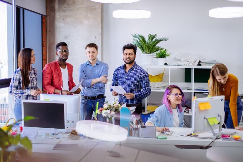 Ungdomargruppen i modernt kontor har diskussion av ett nytt projekt royaltyfria bilder