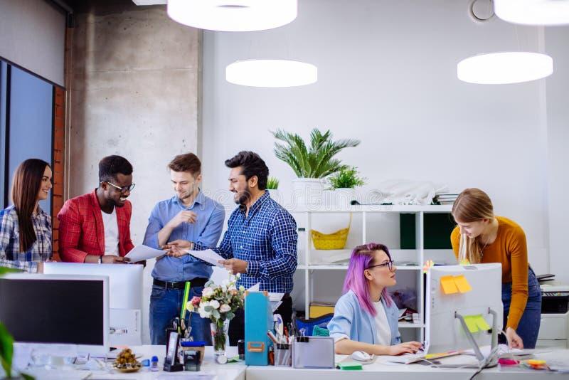 Ungdomargruppen i modernt kontor har diskussion av ett nytt projekt arkivfoton