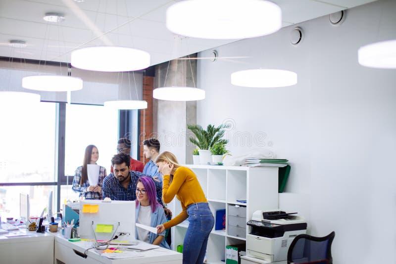 Ungdomargruppen i modernt kontor har diskussion av ett nytt projekt royaltyfri foto
