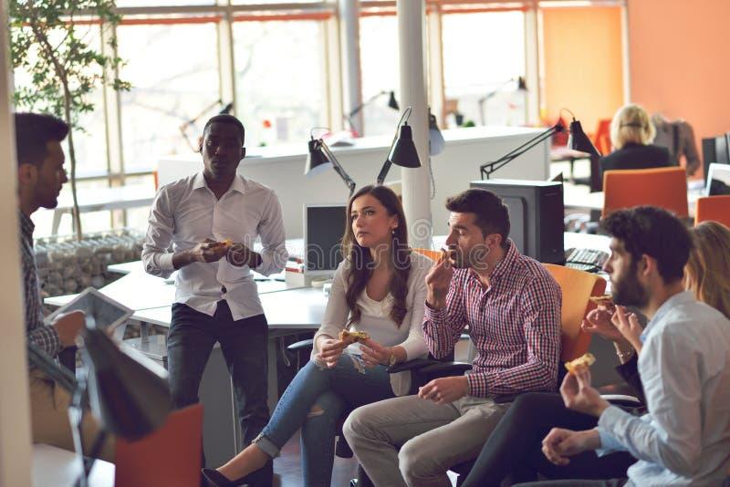 Ungdomargruppen i modernt kontor har lagmöte och idékläckning, medan arbeta på bärbara datorn och dricka kaffe royaltyfri fotografi