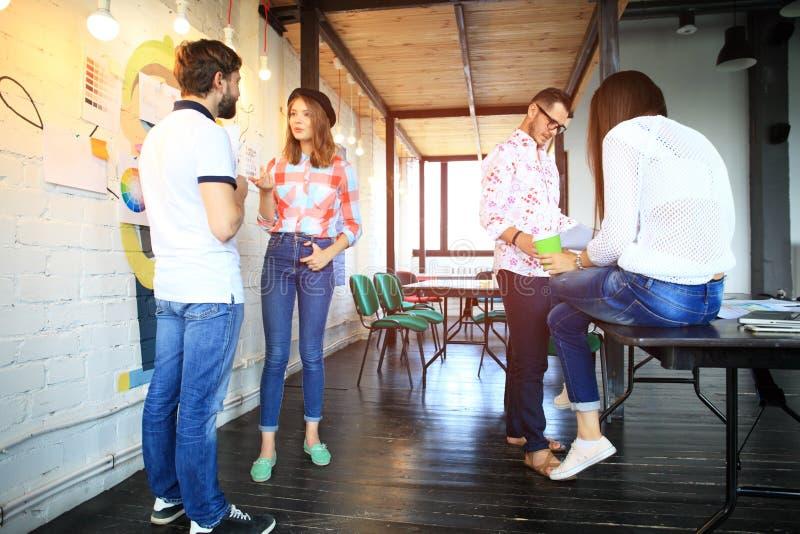 Ungdomargruppen i modernt kontor har lagmöte och idékläckning, medan arbeta på bärbara datorn och dricka kaffe royaltyfria foton