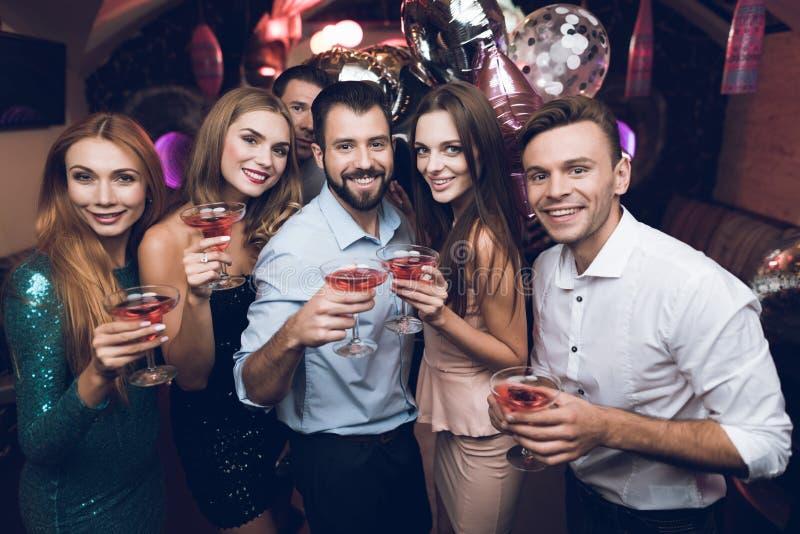 Ungdomarhar gyckel i en nattklubb De dricker coctailar och har gyckel De har gyckel royaltyfri foto