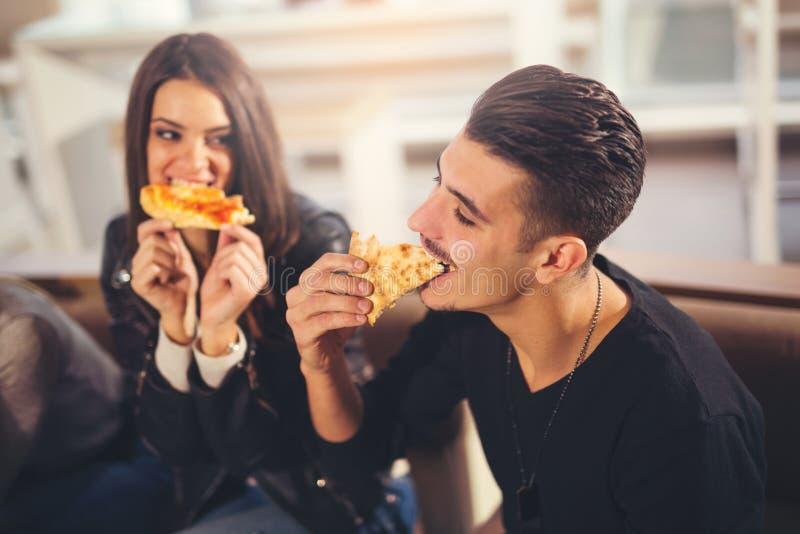Ungdomari tillfällig kläder som äter pizza royaltyfria foton