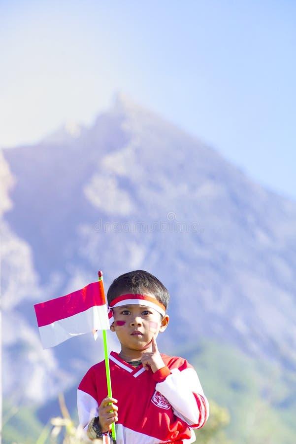 Ungdomarmed flaggan Indonesien flagga, Indonesien självständighetsdagen med bakgrund för mt Merapi arkivfoto
