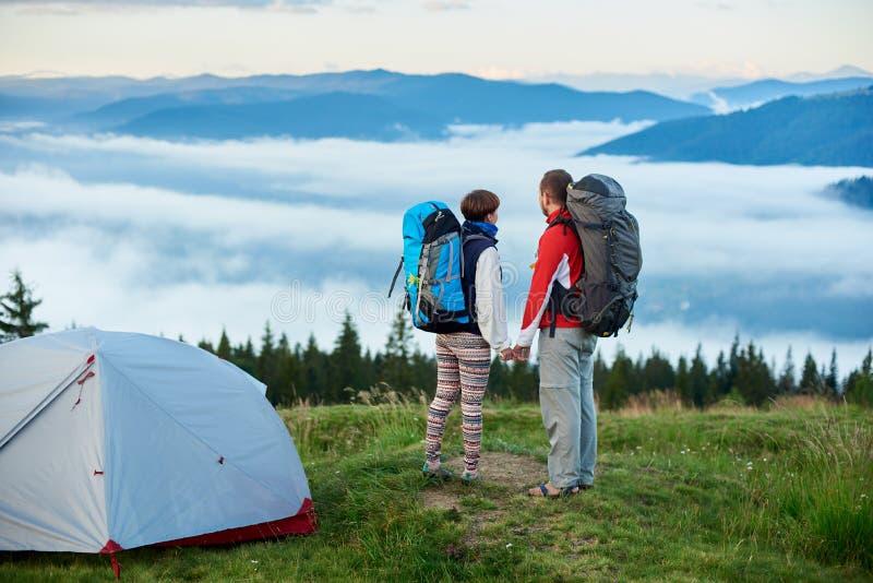 Ungdomarmed near campa hållhänder och blick för ryggsäckar på berg arkivbilder