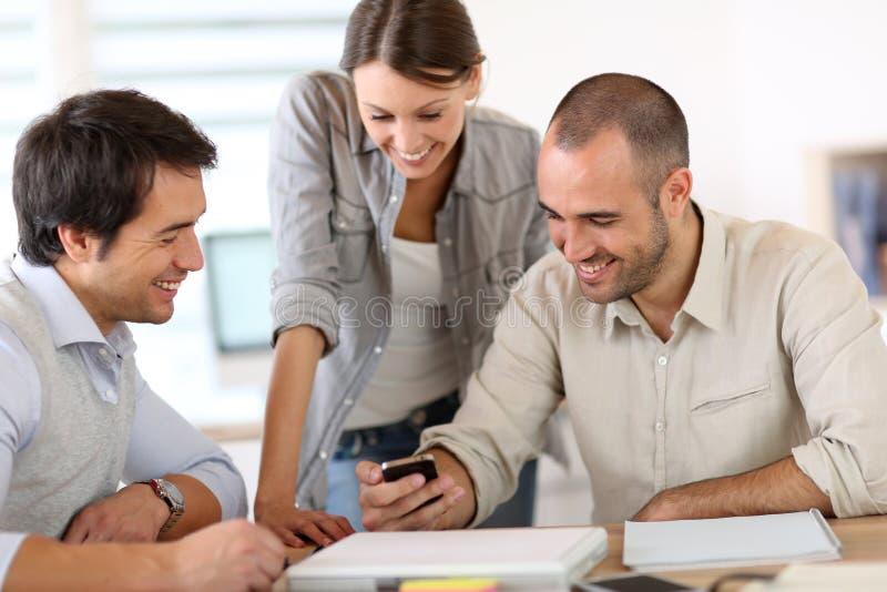 Ungdomarpå kontoret genom att använda smartphonen och att skratta arkivfoton