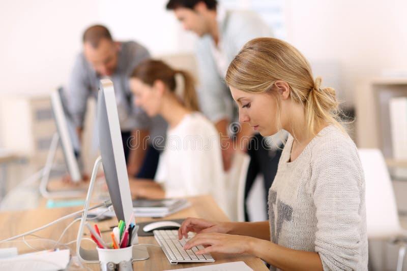 Ungdomarpå kontoret som arbetar på datorer arkivbild