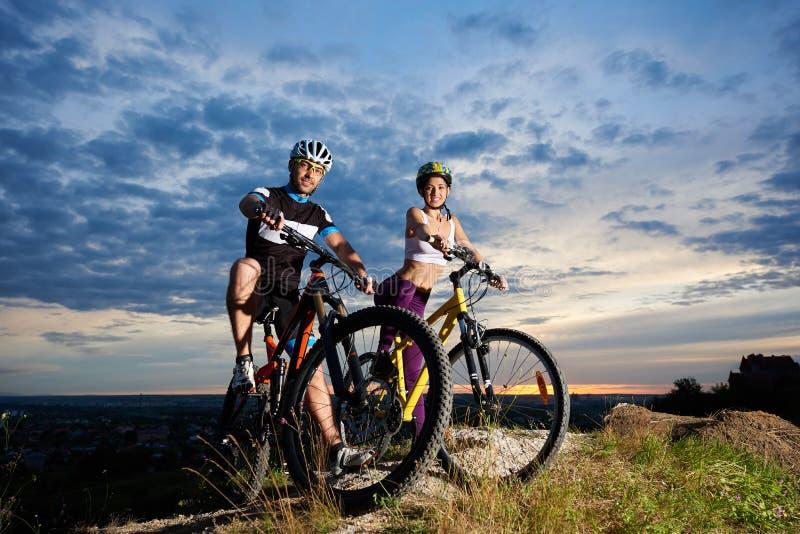 Ungdomarpå mountainbiken överst av kullen under magisk himmel på solnedgången royaltyfri foto