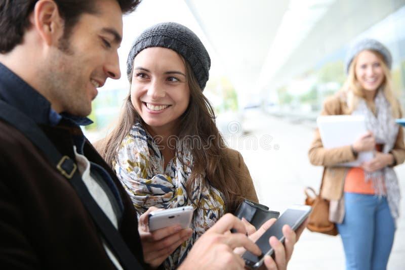 Ungdomarpå skolan genom att använda smartphones arkivfoton