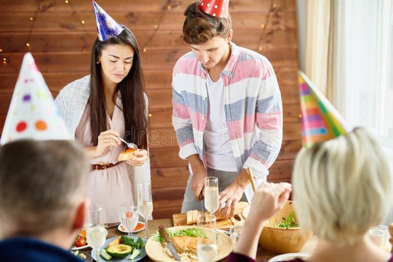 Ungdomarsom äter på födelsedagpartiet royaltyfria bilder