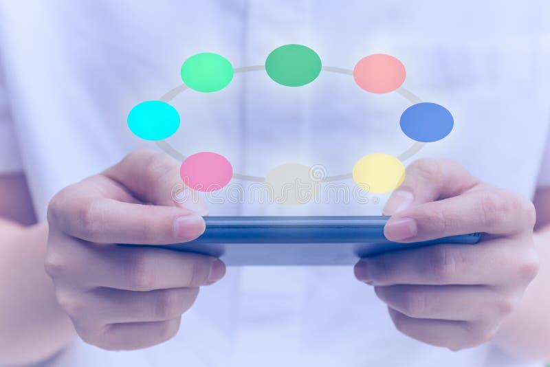 Ungdomarsom använder mobiltelefonen med den digitala symbolen för färgrik cirkel royaltyfria foton