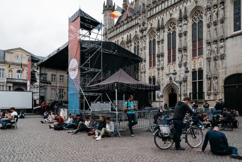 Ungdomarsom använder offentliga WIFI på staden Hall Square i stadsnollan royaltyfri foto