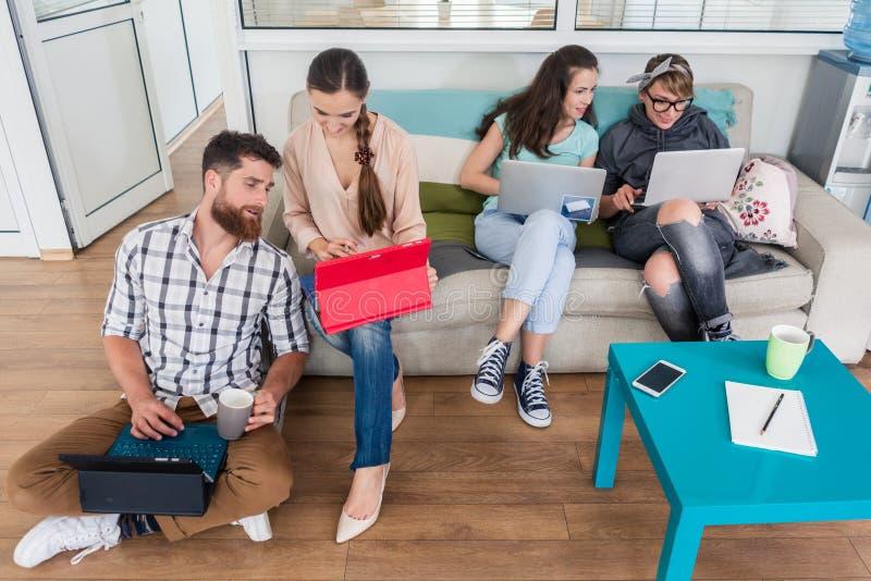Ungdomarsom delar ett kollaborativt kontorsutrymme i en modern hu royaltyfri foto