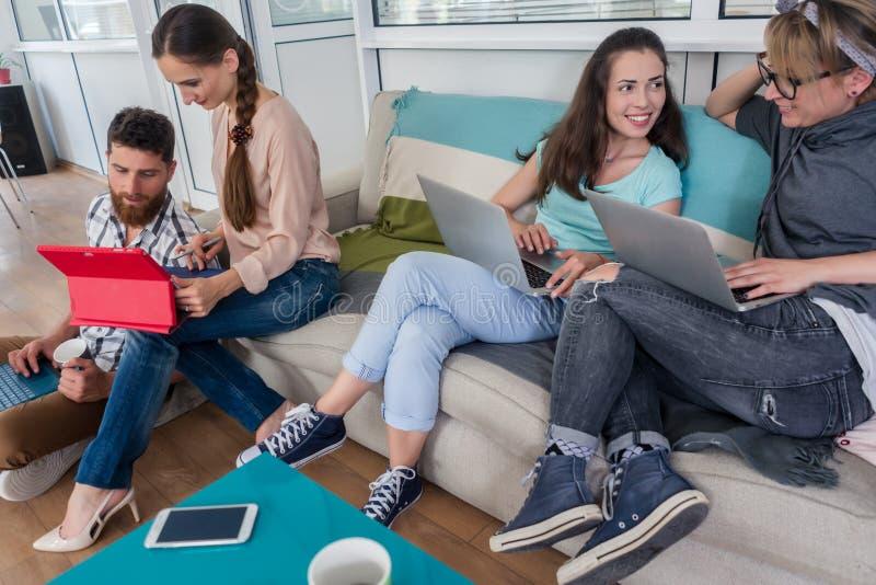 Ungdomarsom delar ett kollaborativt kontorsutrymme i ett modernt nav arkivfoton