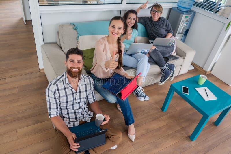 Ungdomarsom delar ett kollaborativt kontorsutrymme i ett modernt nav royaltyfri fotografi