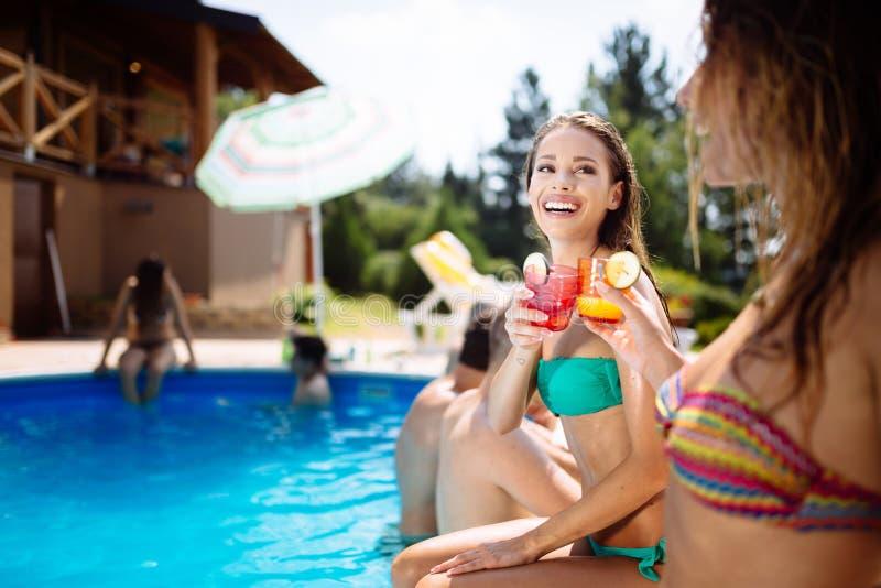 Ungdomarsom dricker coctailar på simbassängen royaltyfria bilder