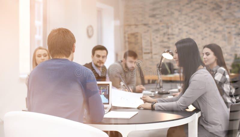 Ungdomarsom har affärsmöte i konferensrum, sikt till och med exponeringsglas royaltyfri bild