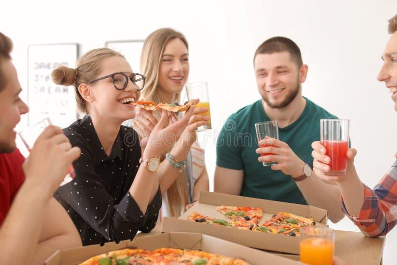 Ungdomarsom har det roliga partiet med läcker pizza arkivbilder