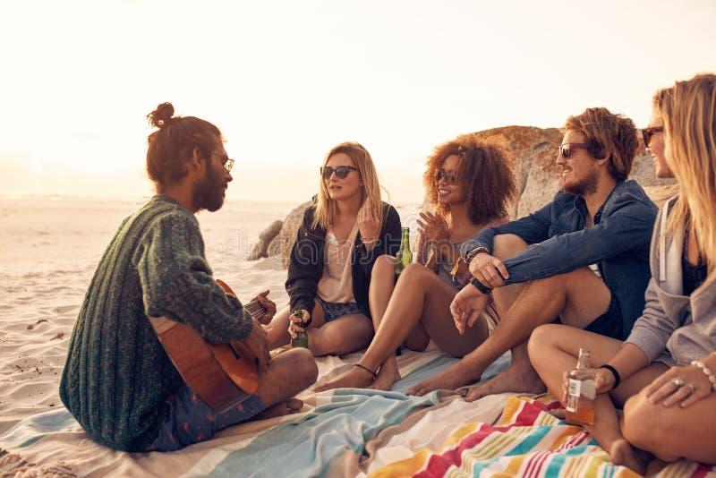 Ungdomarsom har ett parti på stranden royaltyfri fotografi