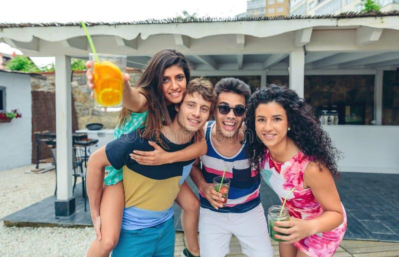 Ungdomarsom har gyckel i sommarparti utomhus royaltyfri fotografi