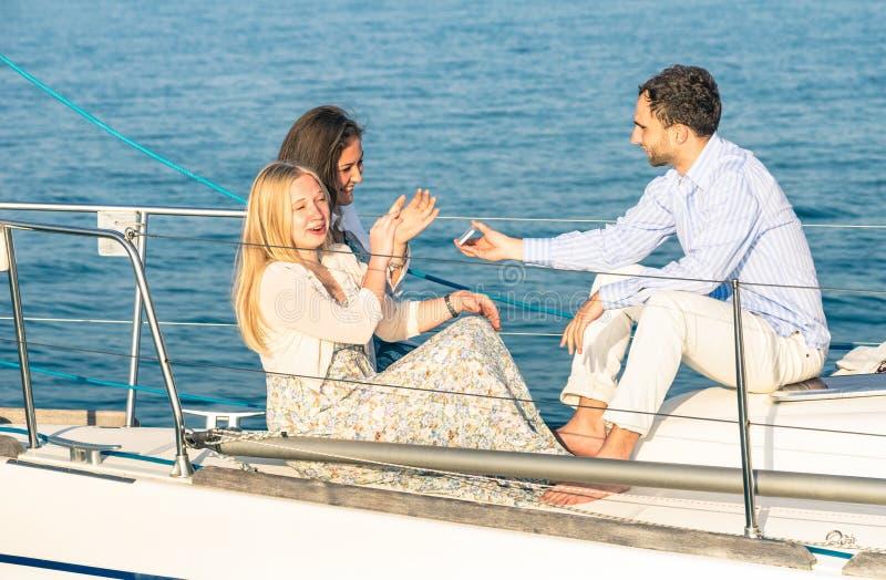Ungdomarsom har gyckel med smartphonen på segelbåten royaltyfri fotografi