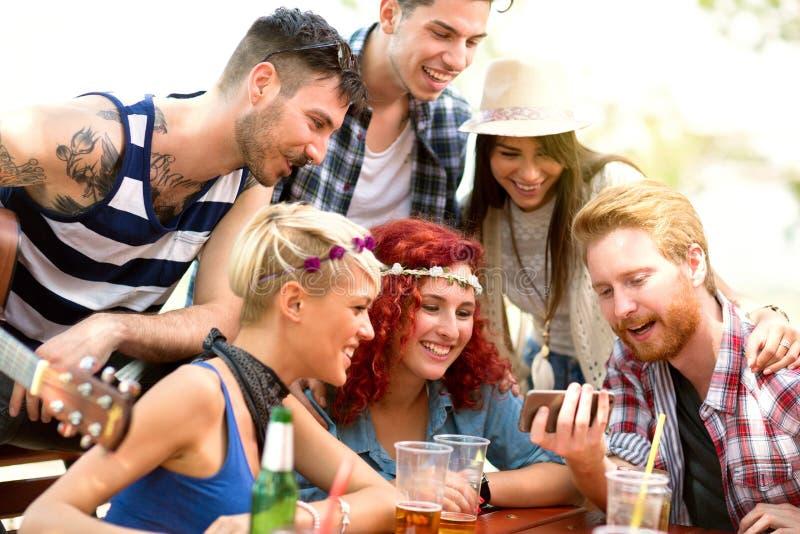Ungdomarsom har gyckel, medan hålla ögonen på något intressera på mobiltelefonen hans vänner arkivbild