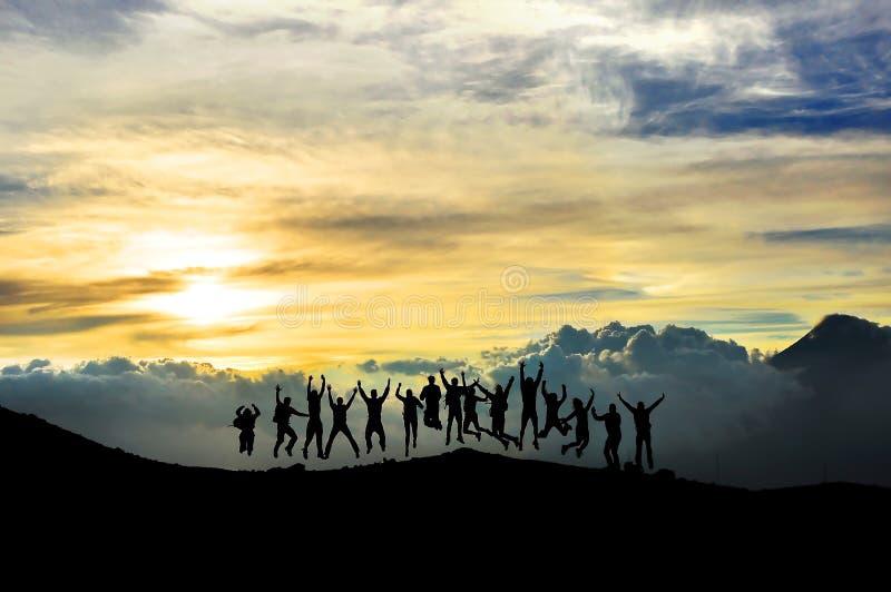 Ungdomarsom hoppar och har gyckel i berget royaltyfria foton